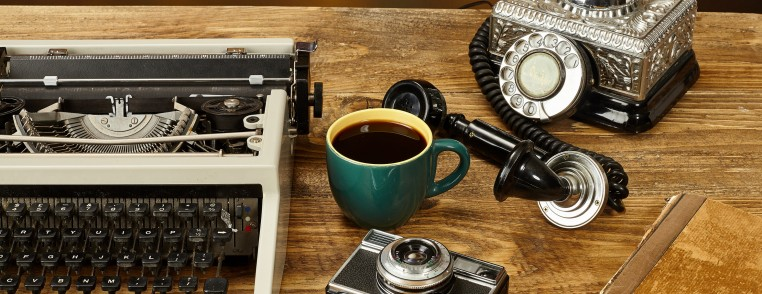 Vintage typewriter, cup of coffee,old telephone,camera and a notebook on wooden table as business concept.