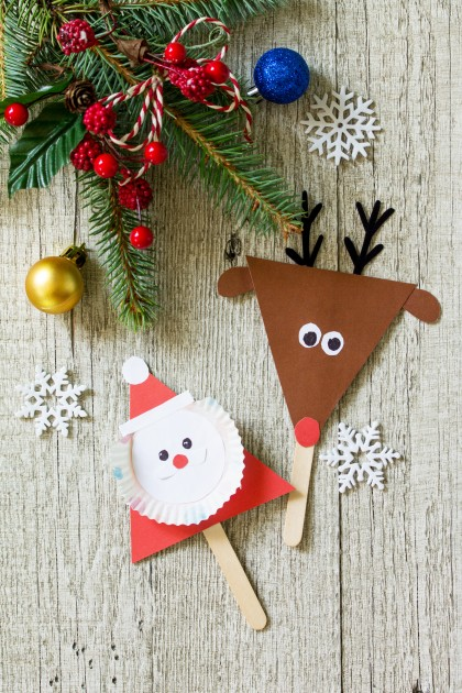 Santa and Reindeer stick gift on wooden table. Handmade. Project of children's creativity, handicrafts, crafts for kids.