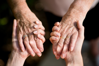 close up of young woman hand holding with tenderness elderly senior person hands