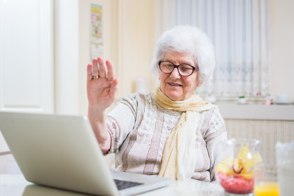 Gray-haired senior woman waving hand in front of laptop while having video call with her family members.
